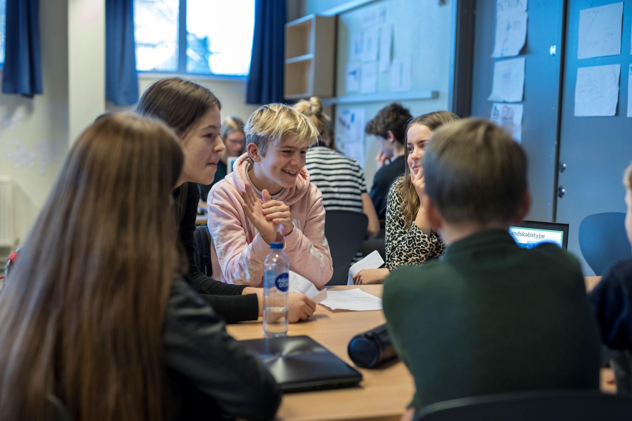 Elever der snakker over et bord